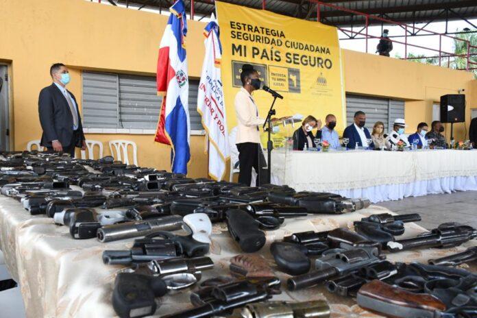 El ministro de Interior y Policía, Jesús Vásquez Martínez, la fiscal Rosalba Ramos y el teniente coronel Iván Gómez, director de la Policía Municipal, observan las armas recolectadas.